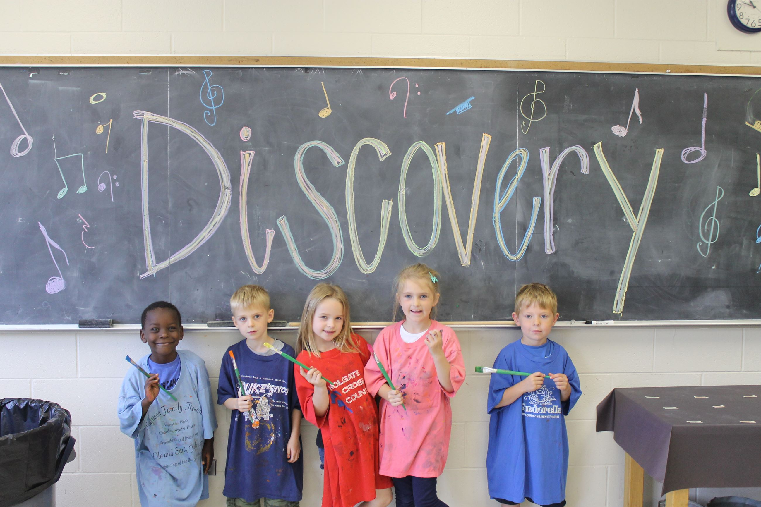 Group of children standing under a Discovery sign on chalk board