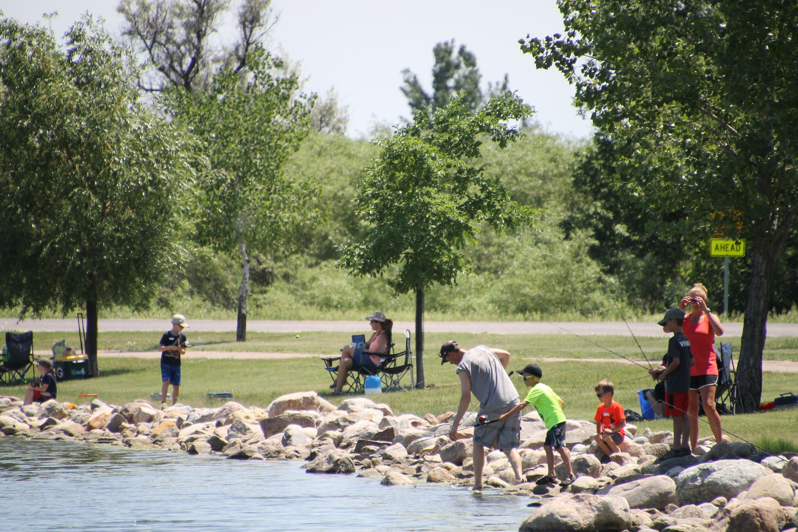 Families standing and sitting around the edge of the lake fishing