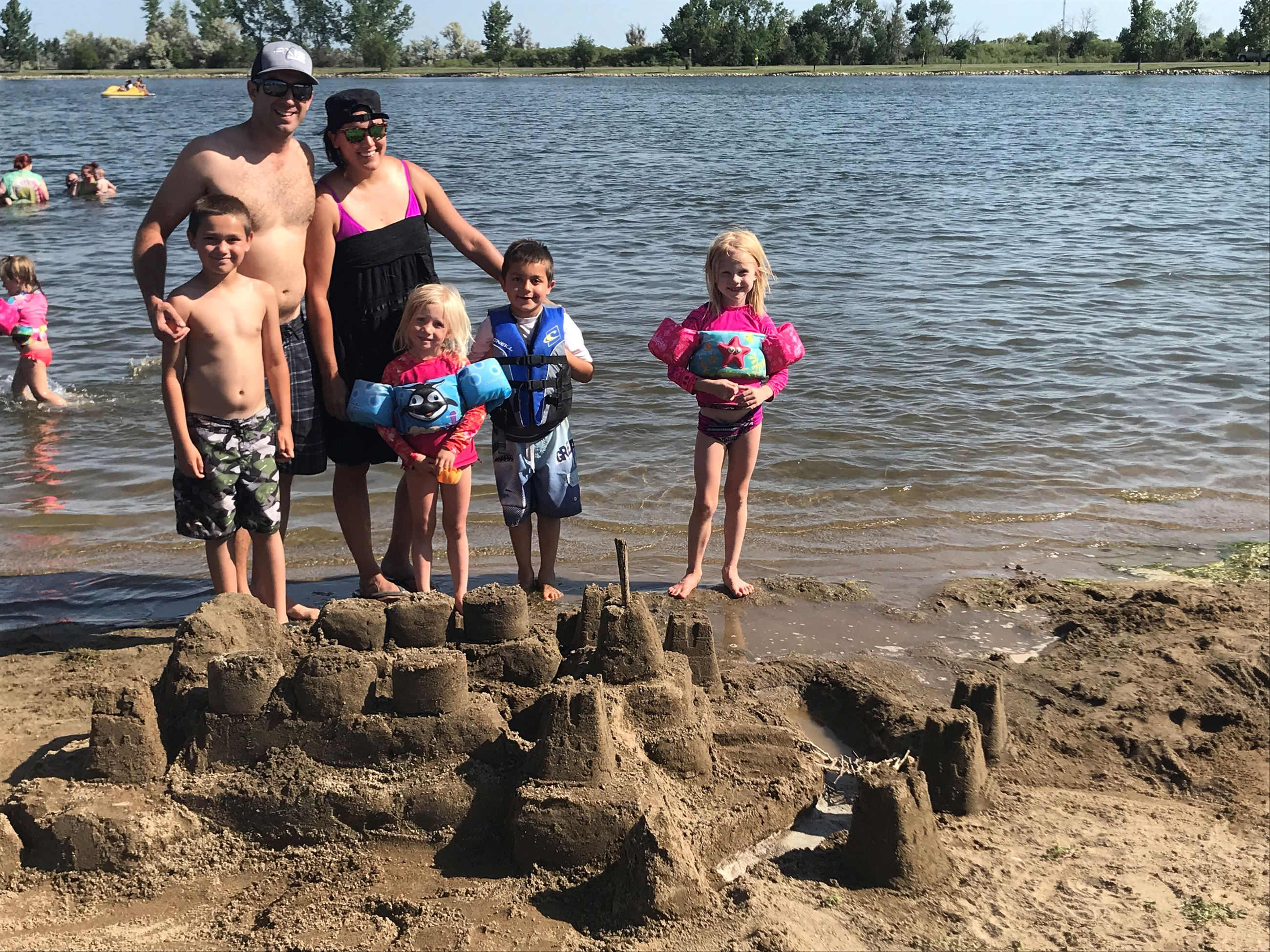 Family standing by their finished Sand Castle Contest Entry