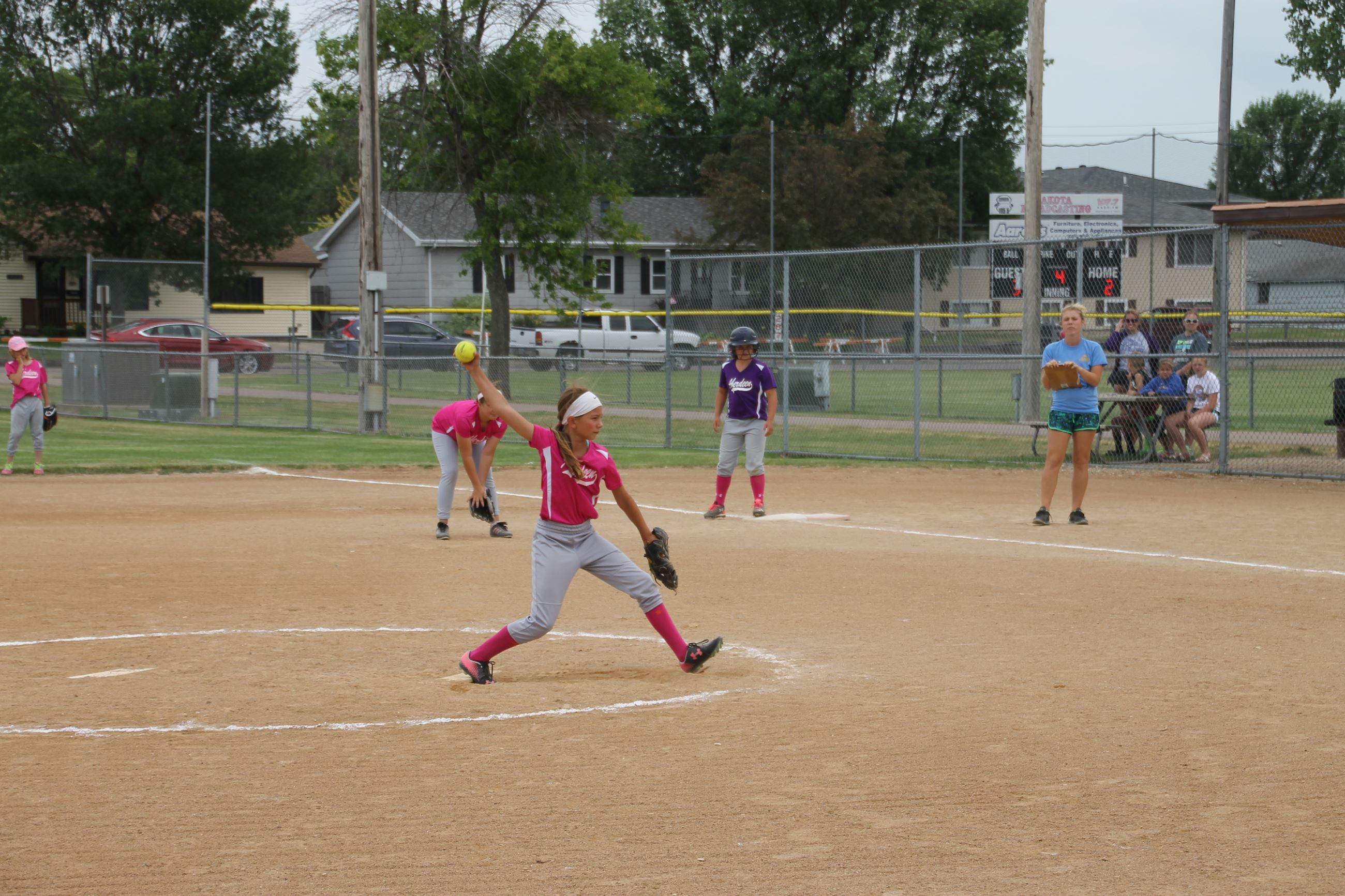 Girl pitching the ball for youth softball